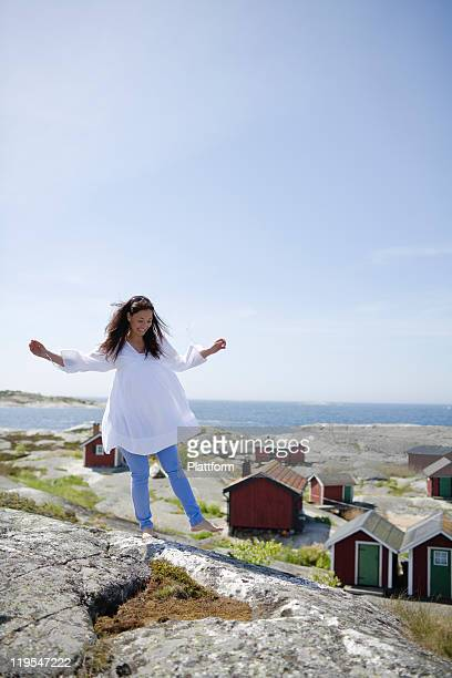woman standing on rock, smiling - one mature woman only stock pictures, royalty-free photos & images