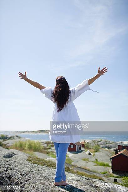 woman standing on rock with arms up - one mature woman only stock pictures, royalty-free photos & images