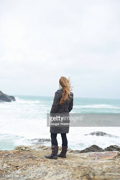 Woman standing on rocks and looking out to sea.