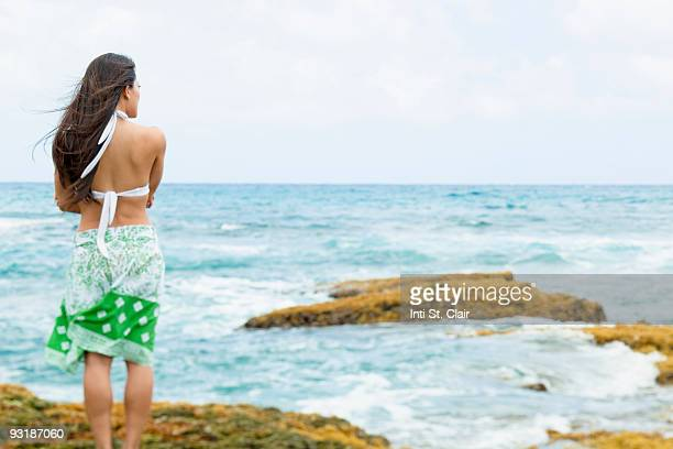 woman standing on rocks looking at stormy ocean - backless stock pictures, royalty-free photos & images