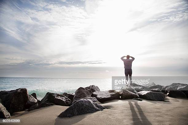 Woman standing on rocks looking out to sea
