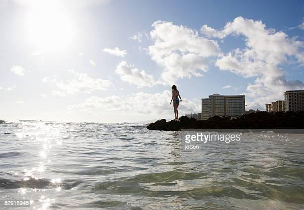 Woman standing on rocks near ocean