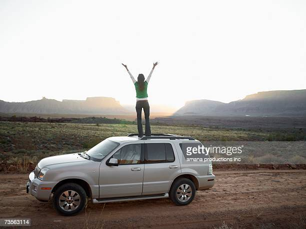 Woman standing on roof of car, arms outstretched, rear view, Moab, Utah, USA