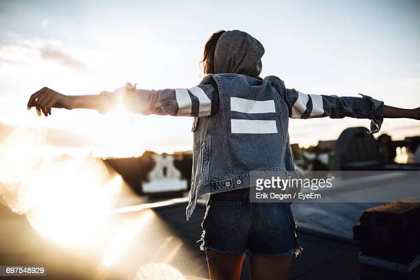 woman standing on rooftop against sky - denim shorts stock pictures, royalty-free photos & images