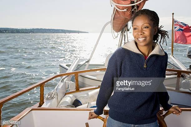 Femme debout sur un bateau à voile dans l'eau