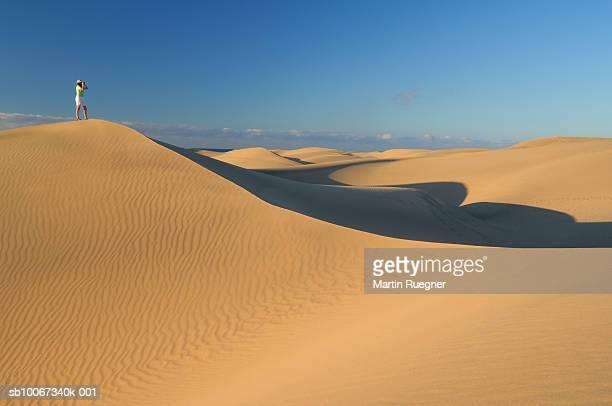 woman standing on sand dune looking over desert - isla de gran canaria fotografías e imágenes de stock