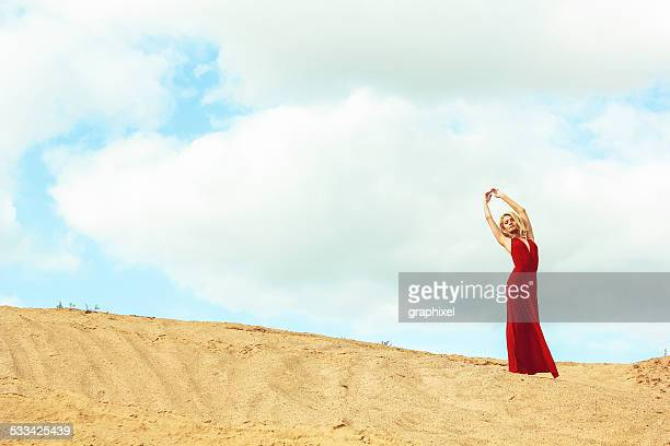 woman standing on sand - graphixel stock pictures, royalty-free photos & images