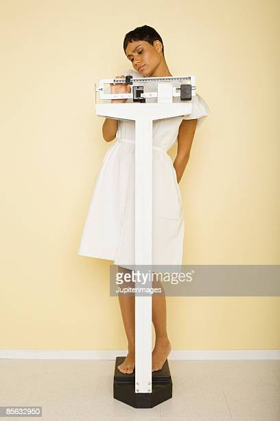 woman standing on scale - mid adult women stock pictures, royalty-free photos & images