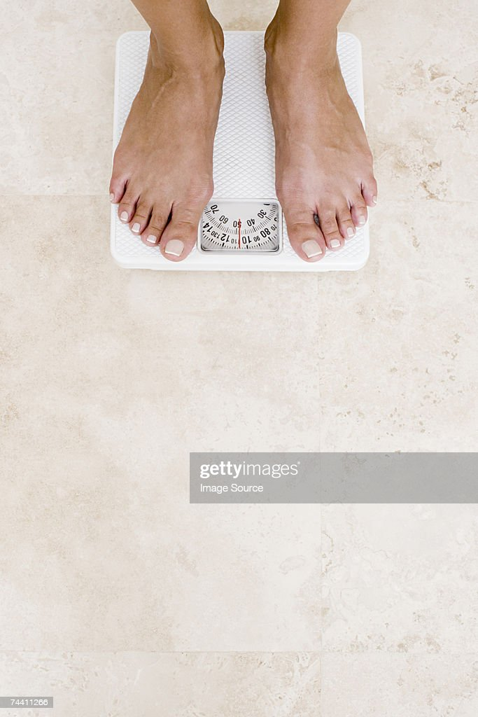 Woman standing on scales : Stock Photo