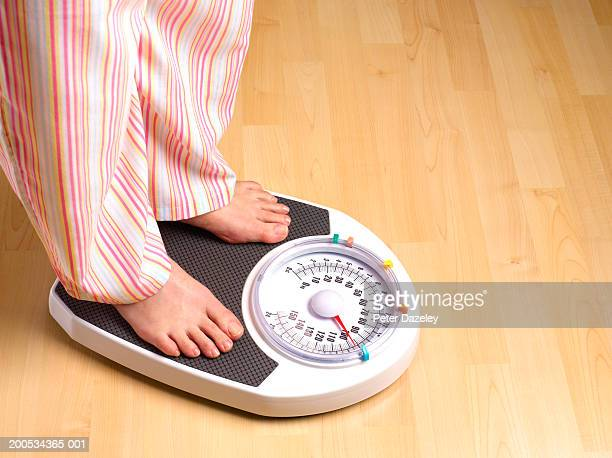 Woman standing on scales, wearing pyjamas, low section