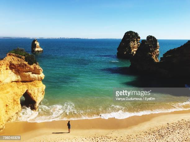 woman standing on sea shore at praia do camilo beach against clear sky - algarve stock photos and pictures
