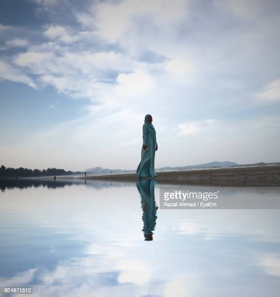 woman standing on shore against sky at beach - wedding veil stock photos and pictures