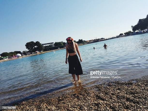 Woman Standing On Shore At Beach