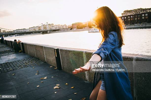 Woman Standing On Sidewalk By River Against Sky During Sunset