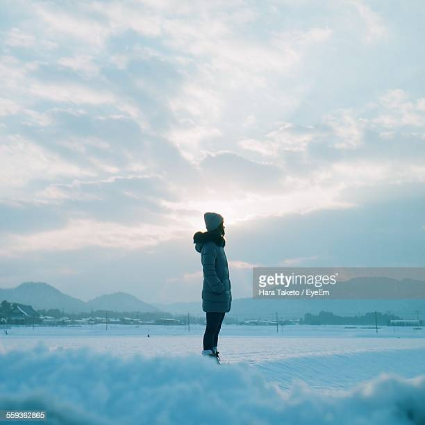 Woman Standing On Snow Covered Field Against Sky