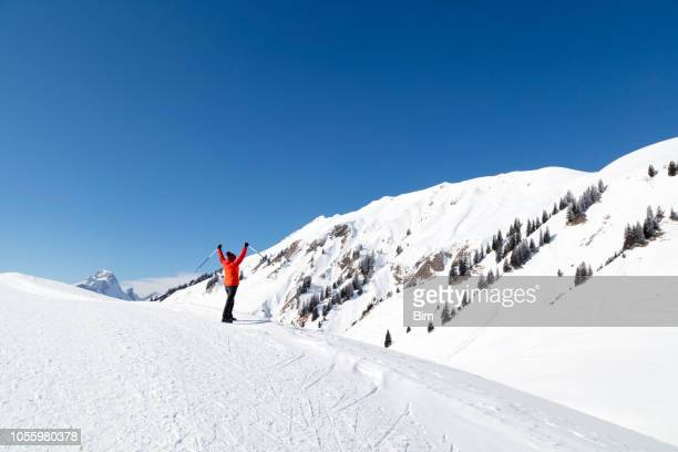 Woman Standing On Snow Covered Mountain With Arms Raised