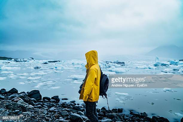 Woman Standing On Snow Covered Shore Against Sky
