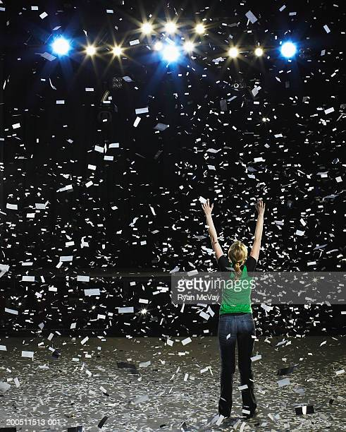 Woman standing on stage raising hands being showered with confetti