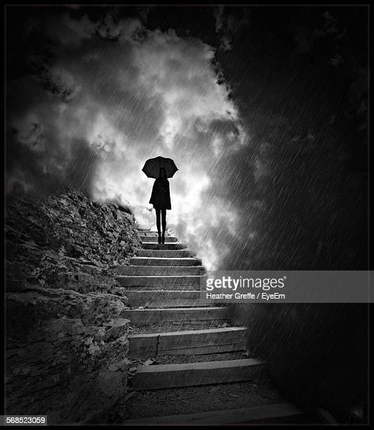woman standing on staircase with umbrella in rain - heather storm stock photos and pictures