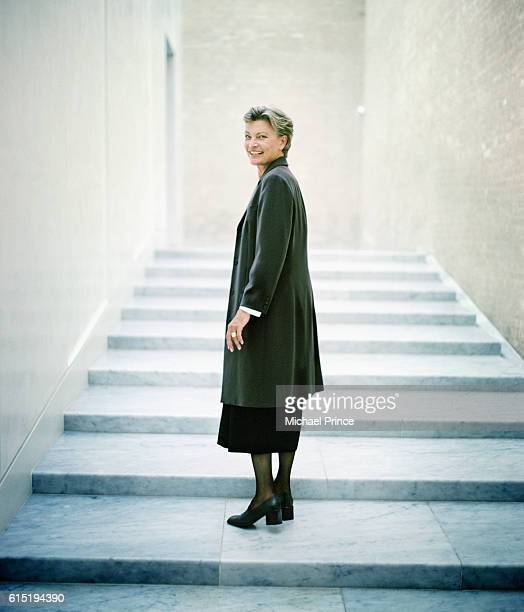woman standing on stairs - looking over shoulder - fotografias e filmes do acervo