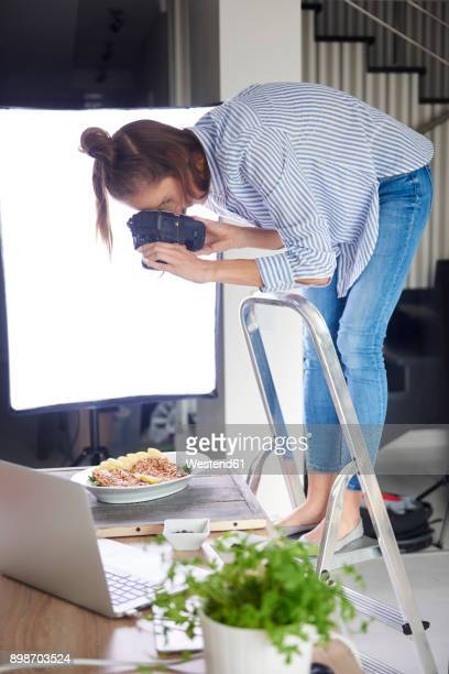 Woman standing on step ladder and photographing food