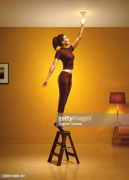 woman standing on stepladder changing light bulb in living room - step ladder stock photos and pictures
