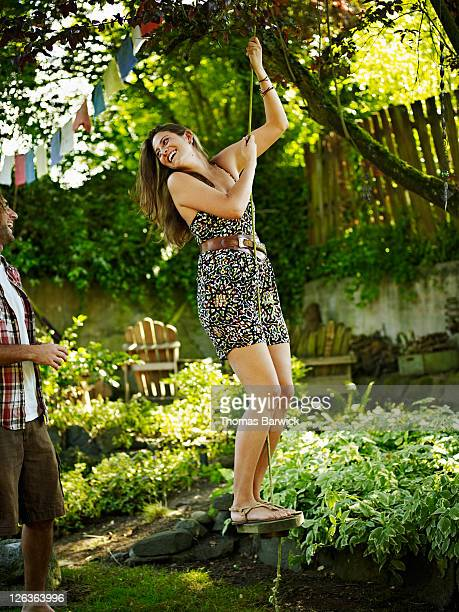 Woman standing on swing in garden