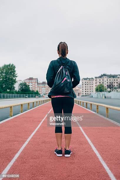 Woman standing on tartan track