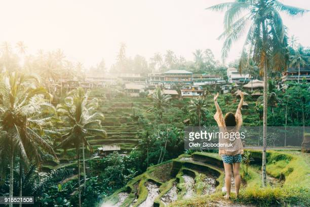 Woman standing on Tegallalang rice field in Bali, Indonesia with her hands up
