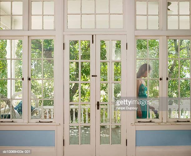 Woman standing on terrace seen through glass door