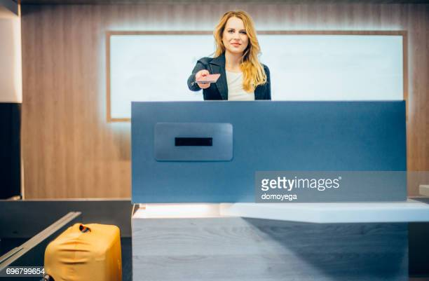 Woman standing on the airport check-in counter and giving passport