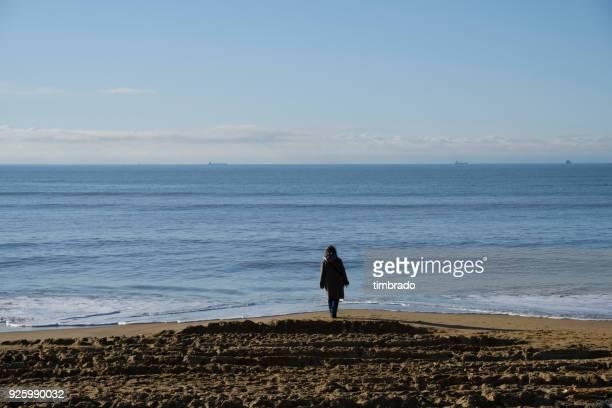 Woman standing on the beach, Chatelaillon, La Rochelle, Nouvelle-Aquitaine, France