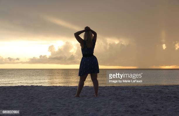 woman standing on the beach pauses by the seashore - fauci stock pictures, royalty-free photos & images