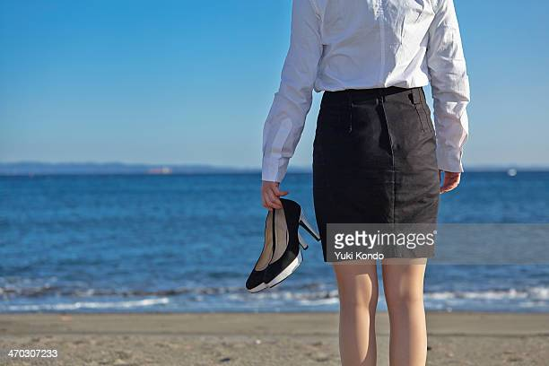 a woman standing on the beach. - japanese short skirts stock pictures, royalty-free photos & images