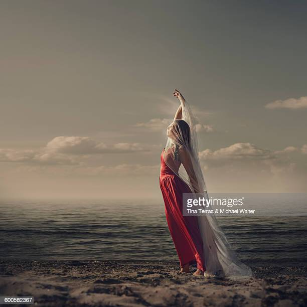 woman standing on the beach - long dress stock pictures, royalty-free photos & images