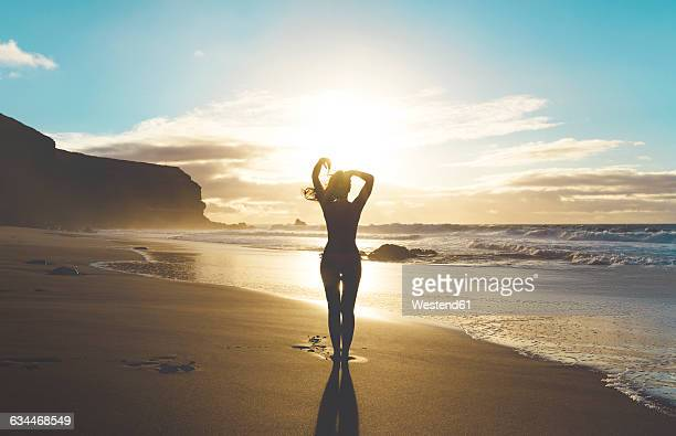 Woman standing on the beach with hands on head at sunset