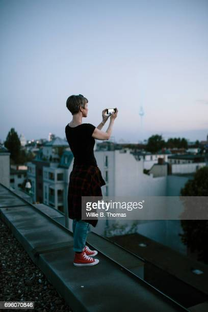 Woman Standing On The Edge Of A Rooftop Taking Photo
