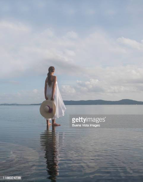 woman standing on the edge of an infinity pool - 白のドレス ストックフォトと画像