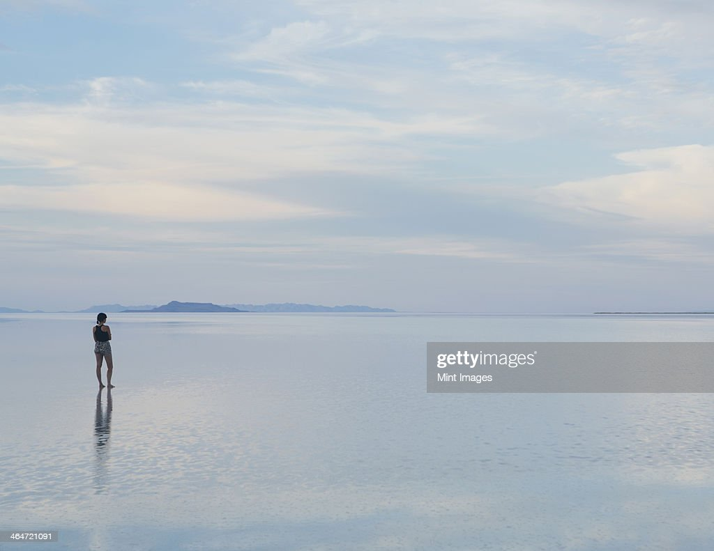 A woman standing on the flooded Bonneville Salt Flats at dusk. Reflections in the shallow water. : Stock Photo