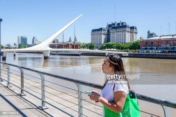A woman standing on the Puente De La Mujer pedestrian suspension swing bridge