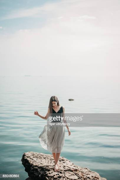 woman standing  on the rock near the sea - one young woman only stock pictures, royalty-free photos & images