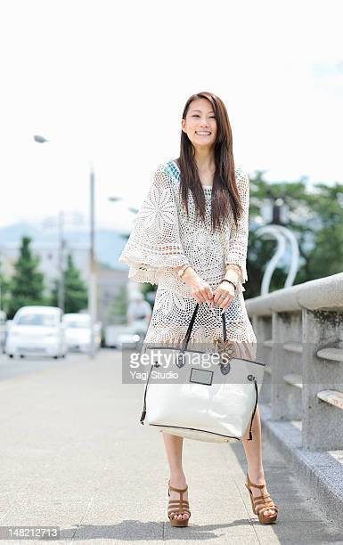 Woman standing on the sidewalk,,smiling