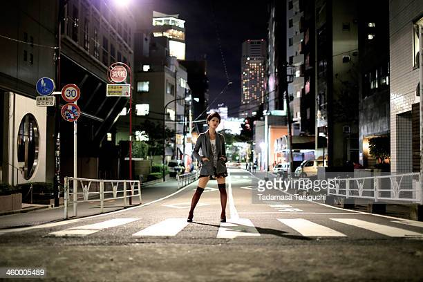 Woman standing on the street at night