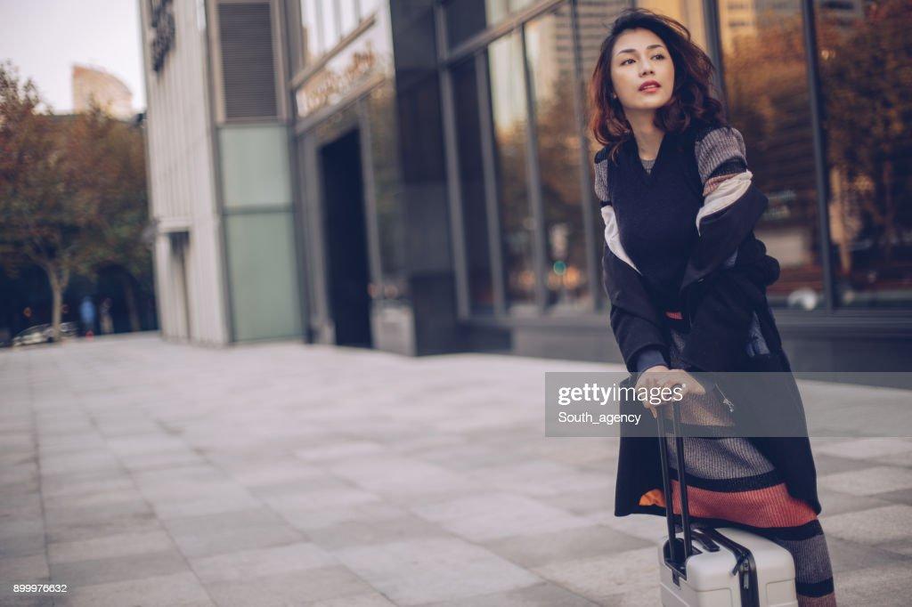 スーツケースで街頭に立っている女性 : ストックフォト