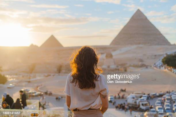 woman standing on the  terrace on the  background of giza pyramids - grand egyptian museum giza stock pictures, royalty-free photos & images