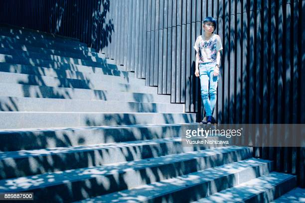 a woman standing on the wall - yusuke nishizawa stock-fotos und bilder