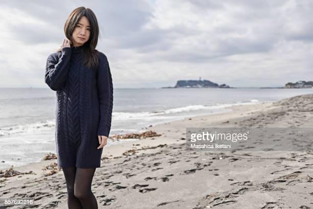 a woman standing on the winter coast - ニットワンピース ストックフォトと画像
