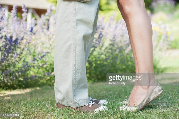 woman standing on tip toe with boyfriend in park - leg kissing stock photos and pictures