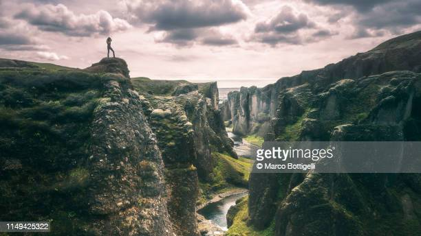 woman standing on top of a canyon in iceland - middlebare afstand stockfoto's en -beelden
