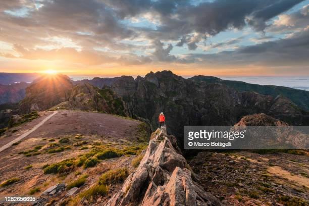 woman standing on top of a rock admiring sunset at pico do arieiro, madeira, portugal - madeira fotografías e imágenes de stock